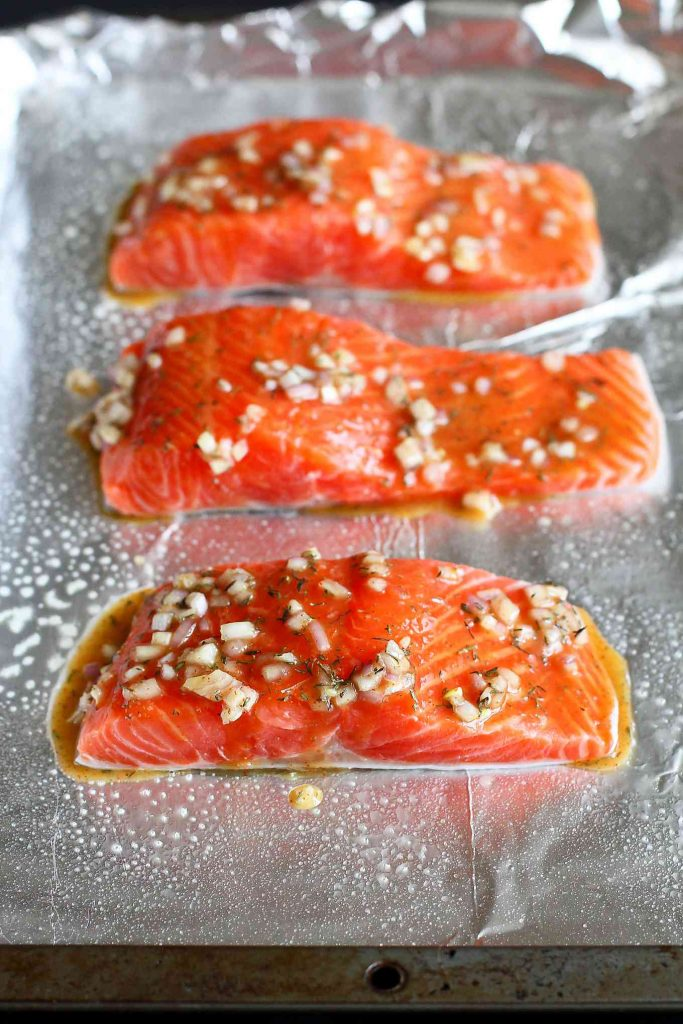 Raw salmon fillets on a foil lined baking sheet, brushed with a glaze.