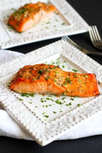 Salmon fillets with a herb glaze on white plates.