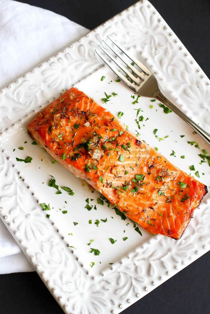 Maple and herb glazed salmon fillets on white plates.