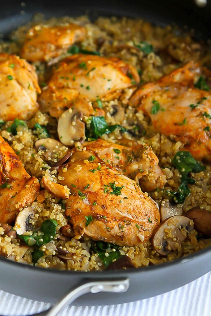 Chicken thighs, cooked quinoa, mushrooms and spinach in a black skillet.
