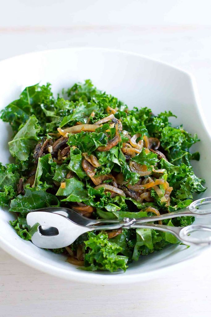 Kale salad with caramelized onions and mushrooms in a white bowl with silver tongs.