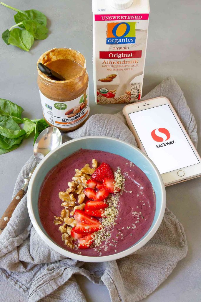 Smoothie bowl, iPhone, almond butter and almond milk on a gray background.