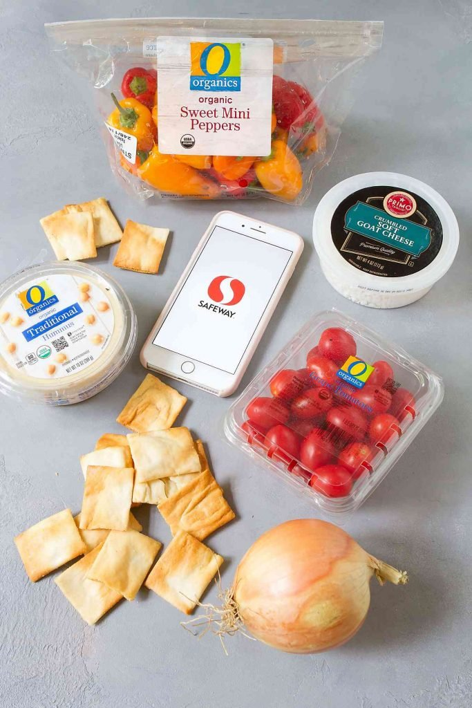 Grape tomatoes, containers of hummus & goat cheese, mini peppers, pita chips and phone with Safeway logo.