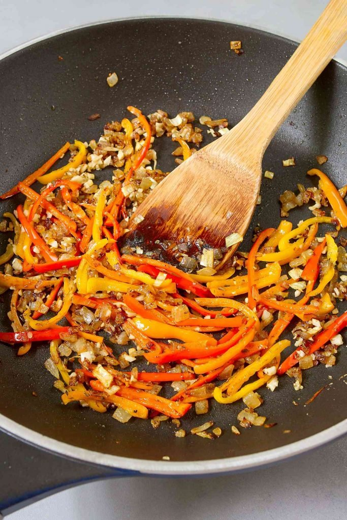 Browned onions and cooked, sliced mini peppers in a nonstick skillet with wooden spatula.