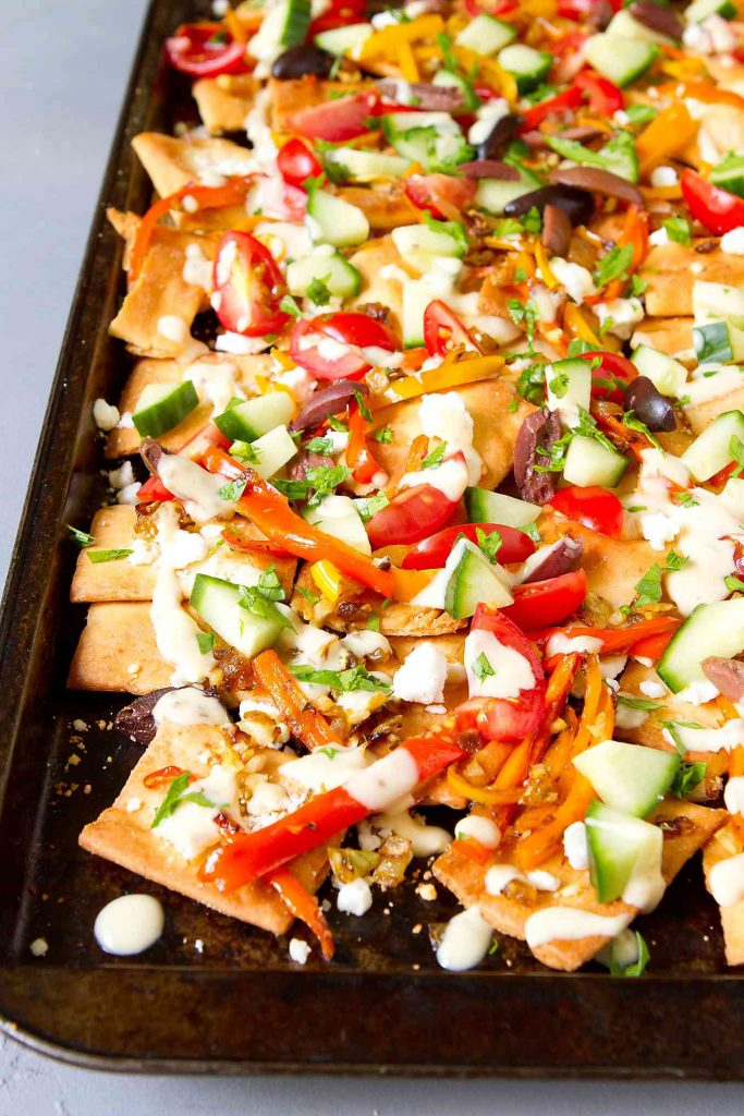 Pita chip nachos on a baking sheet, with goat cheese, hummus dressing and vegetables.