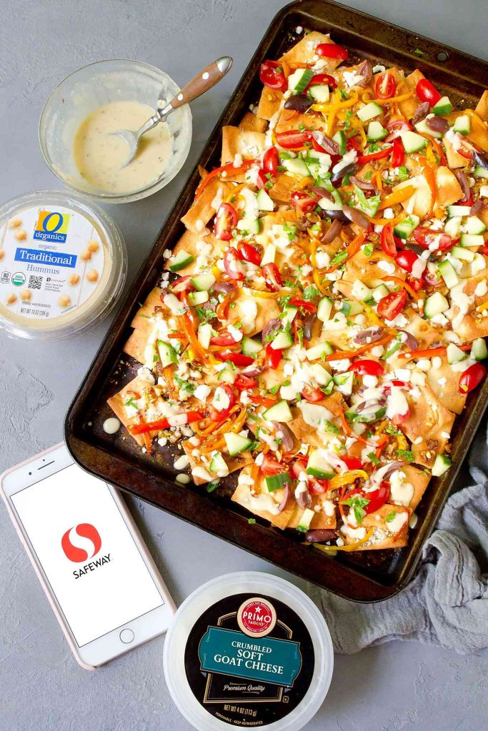 Baking sheet with Mediterranean nachos. Containers of hummus and goat cheese & iPhone on the side.