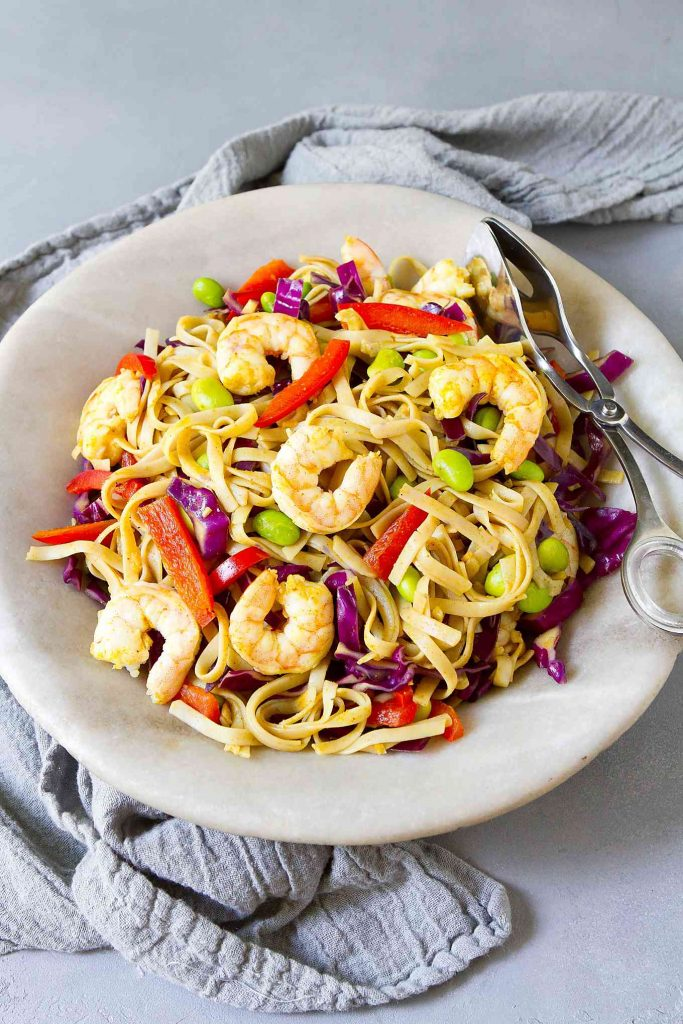 Singapore noodles with shrimp, edamame, cabbage and bell peppers in a stone bowl.