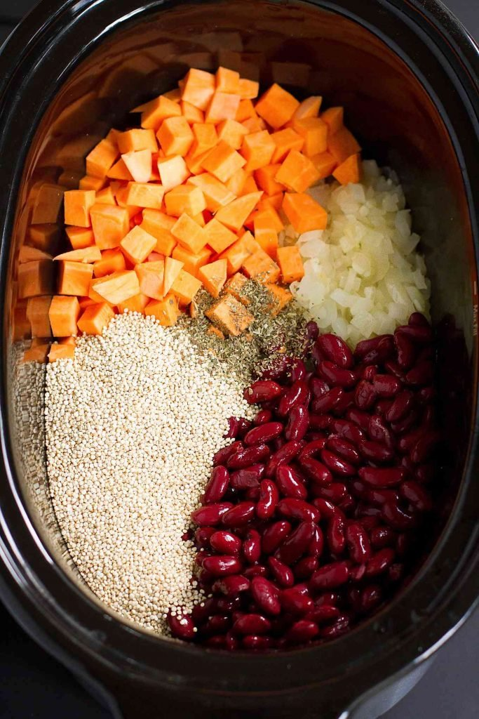 Cubed sweet potato, quinoa, kidney beans, onions and oregano in a crockpot.