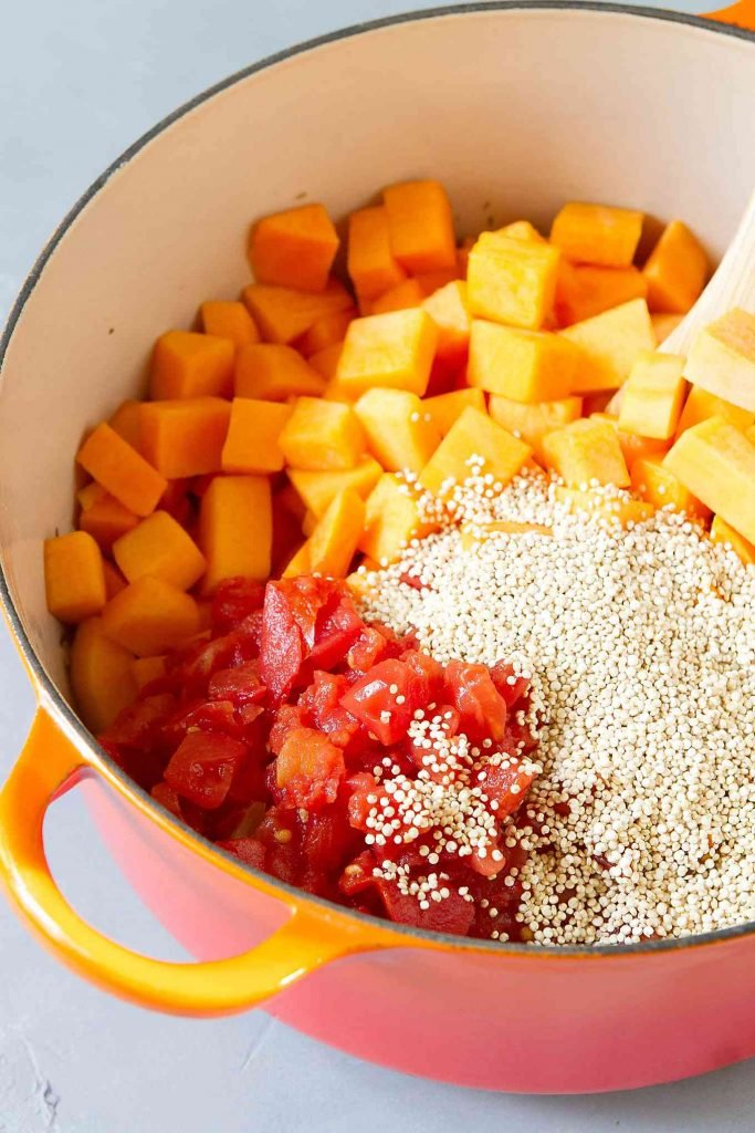 Portakal bir tencerede doğranmış domates, kuşbaşı kabak ve kinoa.