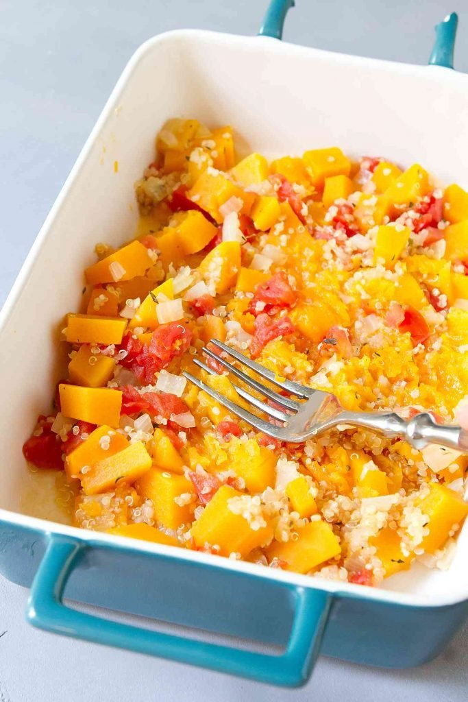Cooked butternut squash, quinoa and tomatoes in a blue dish. Squash being smashed with a fork.