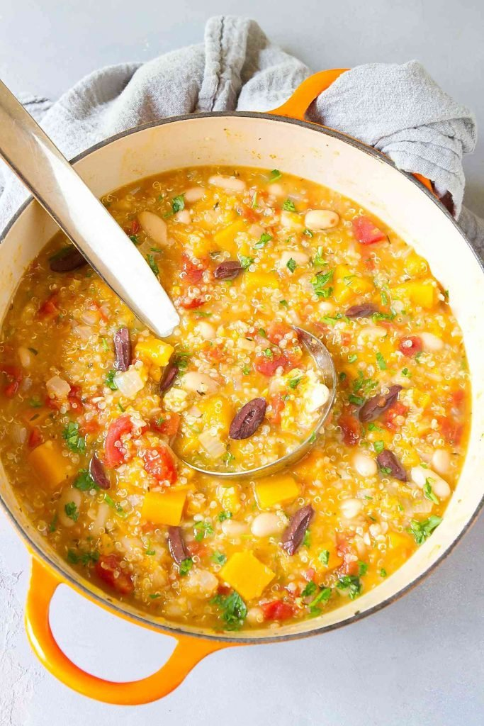 Overhead photo of butternut quinoa stew with beans, in a large saucepan. Gray napkin on the side.