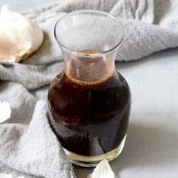 Glass carafe with balsamic vinaigrette, on a gray background with a napkin and garlic cloves.