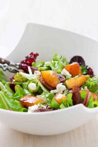 Green salad in a large white bowl, with golden brown pears, goat cheese and wooden salad servers.