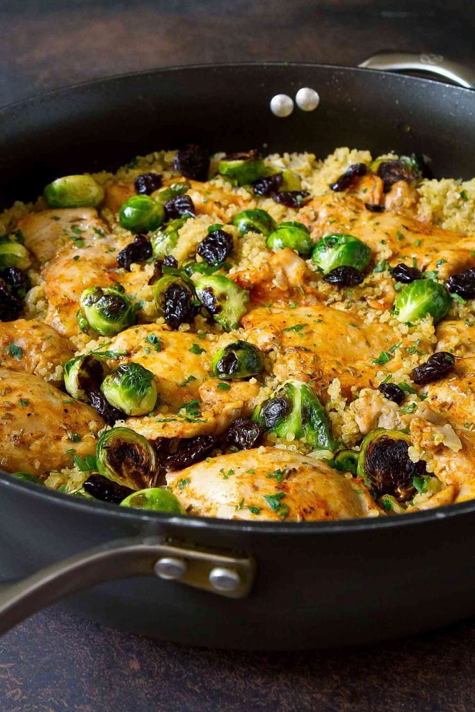 Quinoa, golden brown Brussels sprouts and cooked chicken in a large, black nonstick skillet.