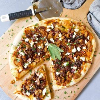 Overhead photo of pizza on pizza peel. With sausage, onions and pumpkin base.