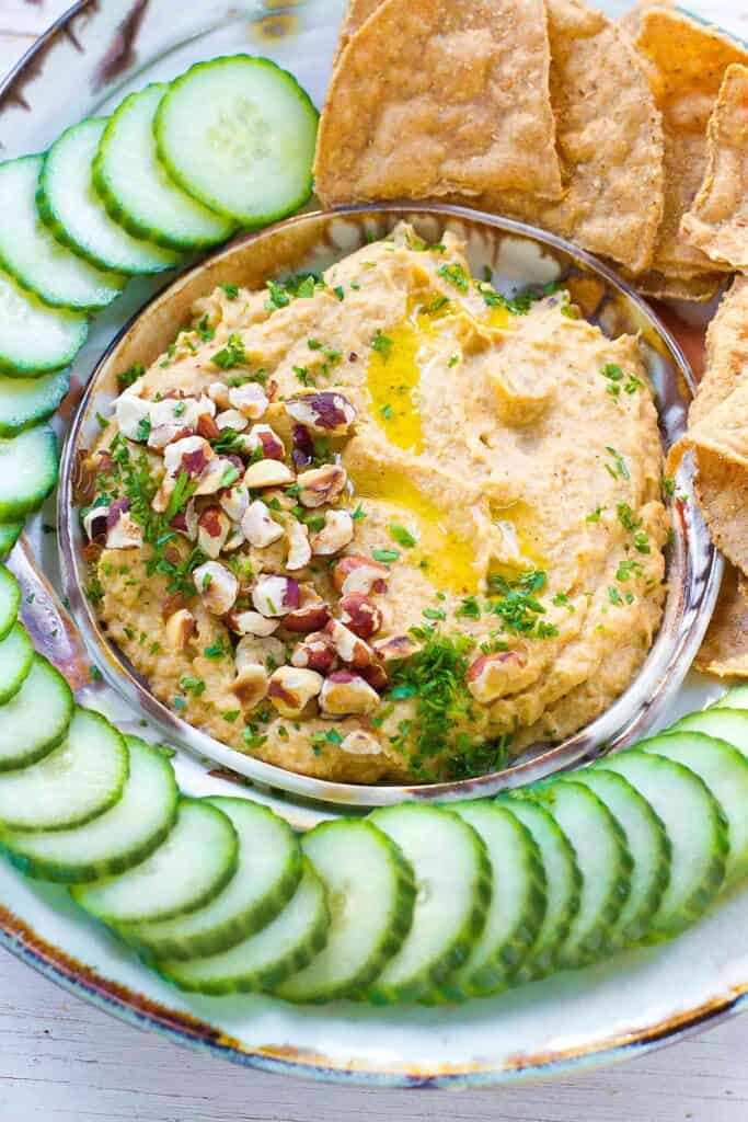 Roasted cauliflower dip with chopped pecans and parsley, surrounded by cucumber slices.