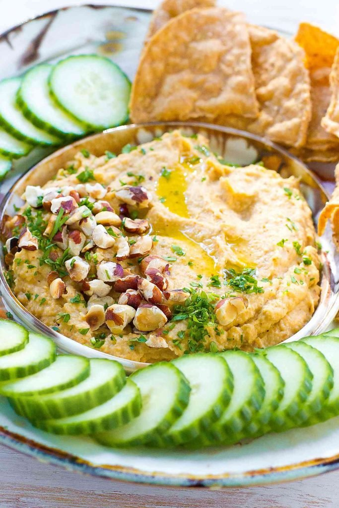 Spiced cauliflower dip in a bowl, topped with hazelnuts. Cucumber slices on the side.