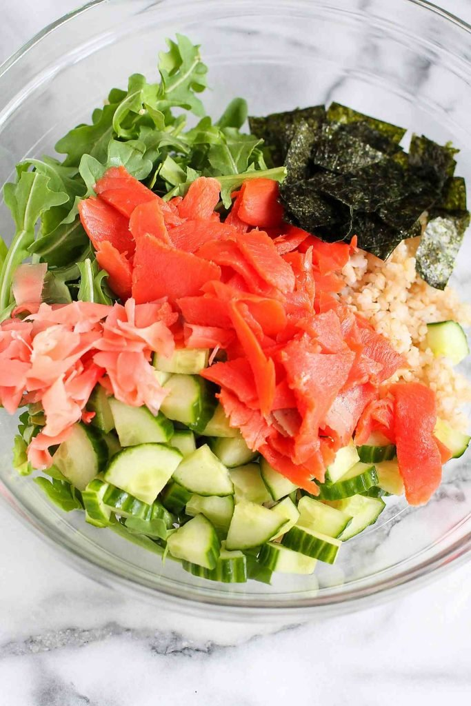 Arugula, smoked salmon, pickled ginger, rice and chopped nori in a glass bowl.