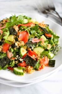 Salad with salmon, nori, cucumber, rice, ginger and arugula on a white plate.