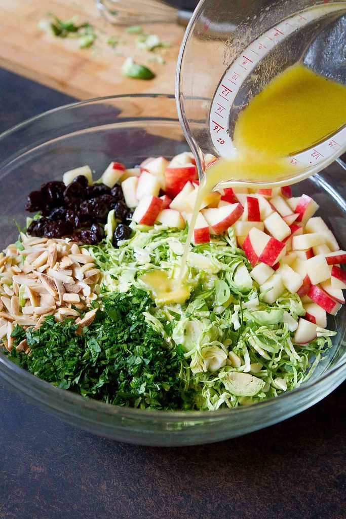 Pouring vinaigrette onto a shredded Brussel Sprouts salad in a glass bowl. With apple and dried cherries.