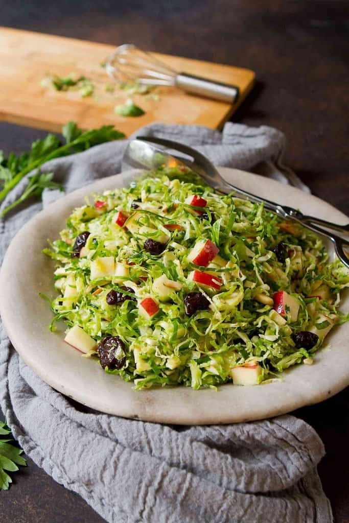 Quick & easy! Serve up this Shredded Brussels Sprouts Salad with your holiday meal. Tossed with apples, toasted almonds and a homemade apple cider vinaigrette. 145 calories and 5 Weight Watchers SP | Vegan | Plant Based | Gut Health | Shaved | Recipes | Fall | Chopped | Brussel sprouts #brusselssproutssalad #brusselsproutssalad #brusselssprouts #brusselsprouts #plantbased #vegansalads #weightwatchers