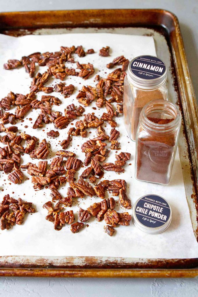 Chopped spiced pecans on a baking sheet lined with parchment paper. Spice bottles on the side.