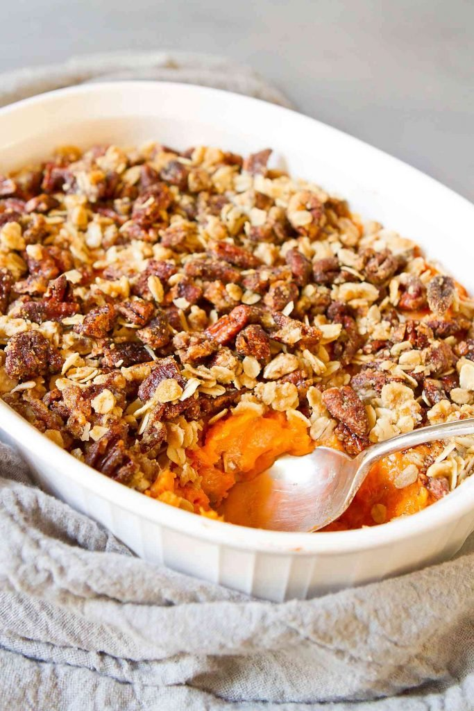 Healthy baked sweet potato casserole in a white baking dish. Spoon scooping out a portion.