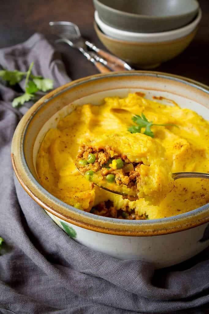 Scoop of shepherd's pie on a silver serving spoon. Casserole dish of shepherd's pie below.