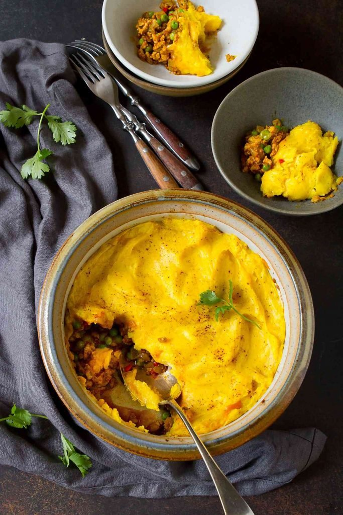 Overhead photo of turmeric-tinted shepherd's pie in a casserole dish. Individual servings in two pottery bowls.