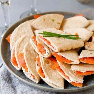 Mini quesadillas filled with cream cheese and smoked salmon, piled on dark gray plate. Glass of Prosecco behind.