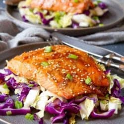 Teriyaki salmon fillet on bed of stir-fried cabbage, on dark brown plate.