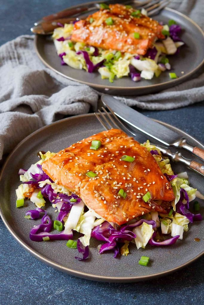 Two dark gray plates with baked teriyaki salmon, sauteed cabbage and wooden handled knife and fork.