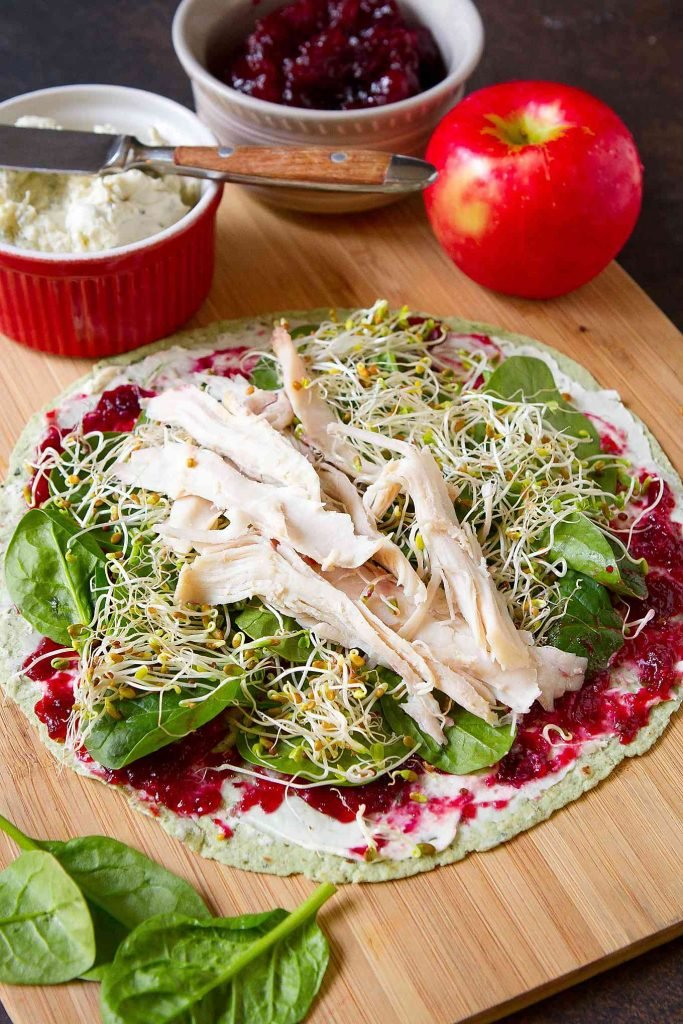 Open tortilla layered with cream cheese, cranberry sauce, turkey, broccoli sprouts and spinach. Ingredients in background.