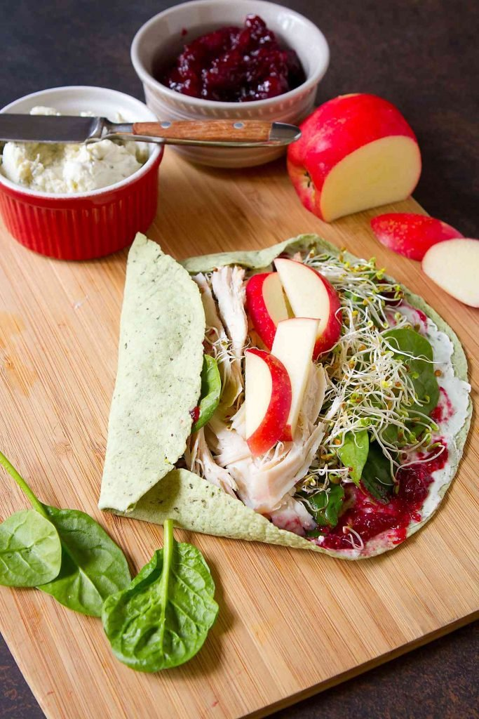 Tortilla with turkey, apple, vegetables and cranberry sauce, partially rolled. Apple and bowls in background.