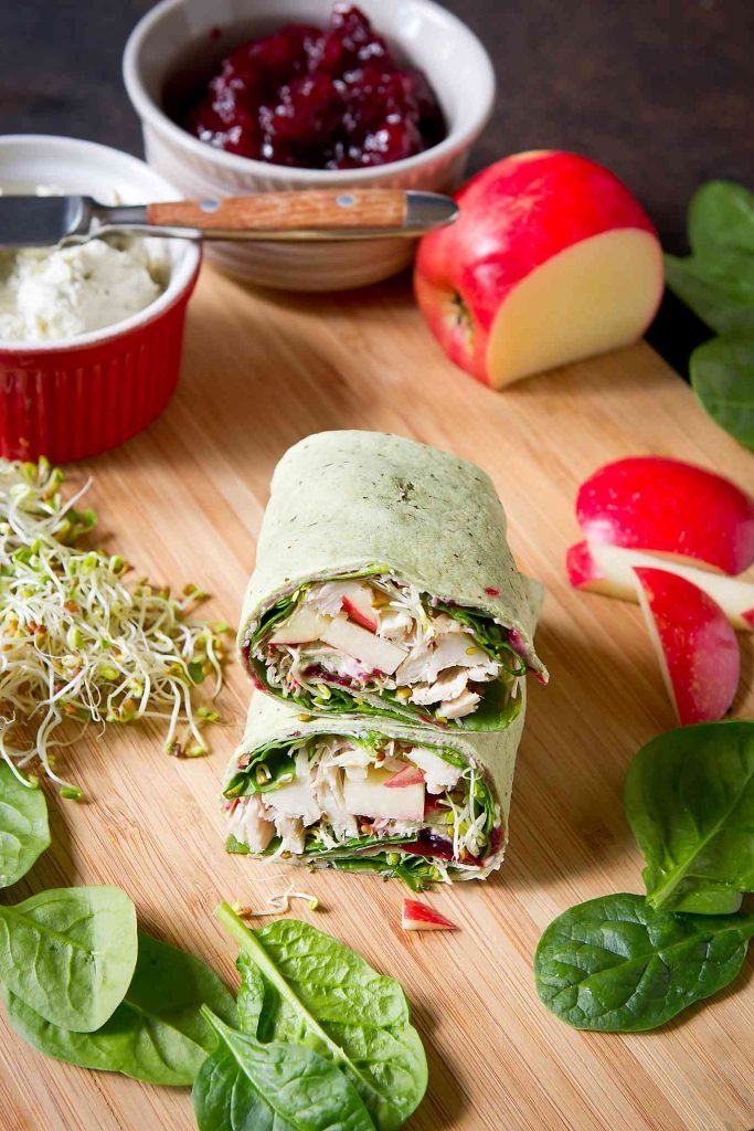 Turkey wrap sandwich cut in half and stacked. Apple and bowls of cranberry sauce and cream cheese on cutting board.