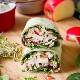 Turkey, cranberry and vegetable wrap sandwich. Apple, broccoli sprouts and bowls in the background.