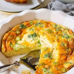 Broccoli cheddar quiche in a pie dish with a wedge cut out. Piece of quiche on a plate in background.