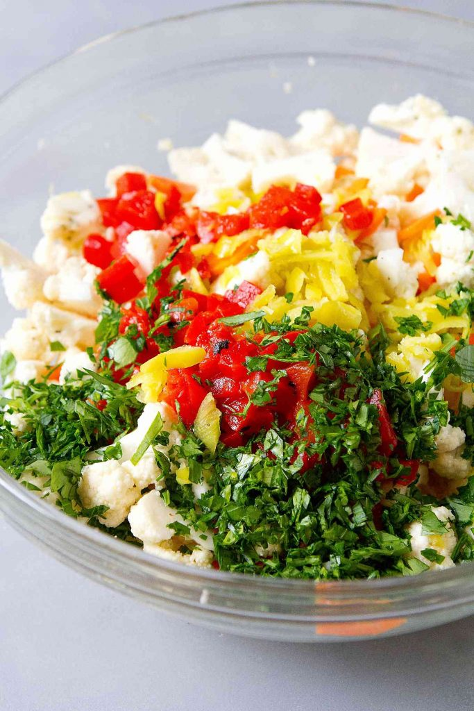 Cauliflower florets, chopped roasted red pepper, pepperoncini and parsley in a glass bowl.