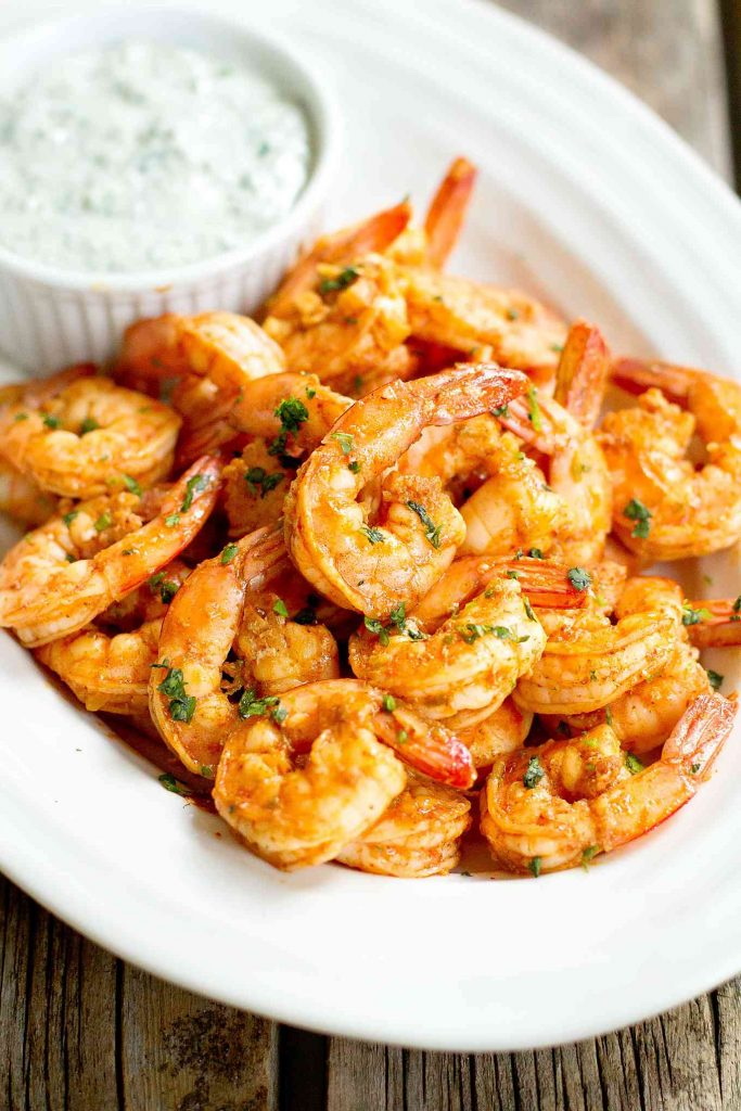 Spice coated cooked shrimp on a white plate, with bowl of yogurt dip behind.