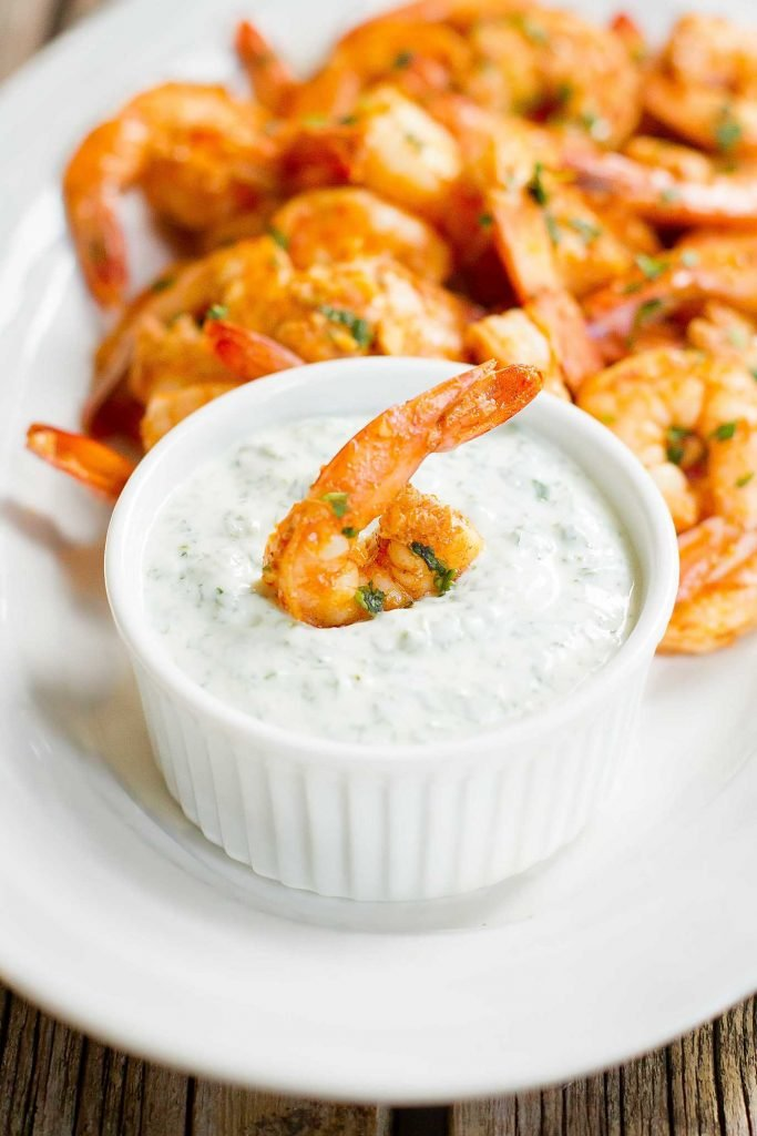 Single cooked shrimp dipping into a bowl of yogurt sauce. Sitting on plate with more shrimp.