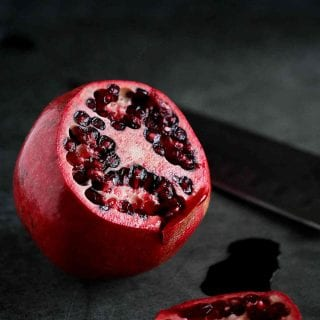 Pomegranate with one side cut off, seeds exposed, with black background.