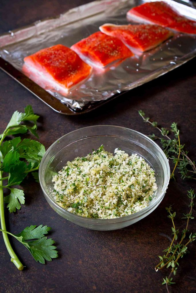 Small glass bowl filled with breadcrumbs, herbs and Parmesan cheese. Salmon fillets in the background.