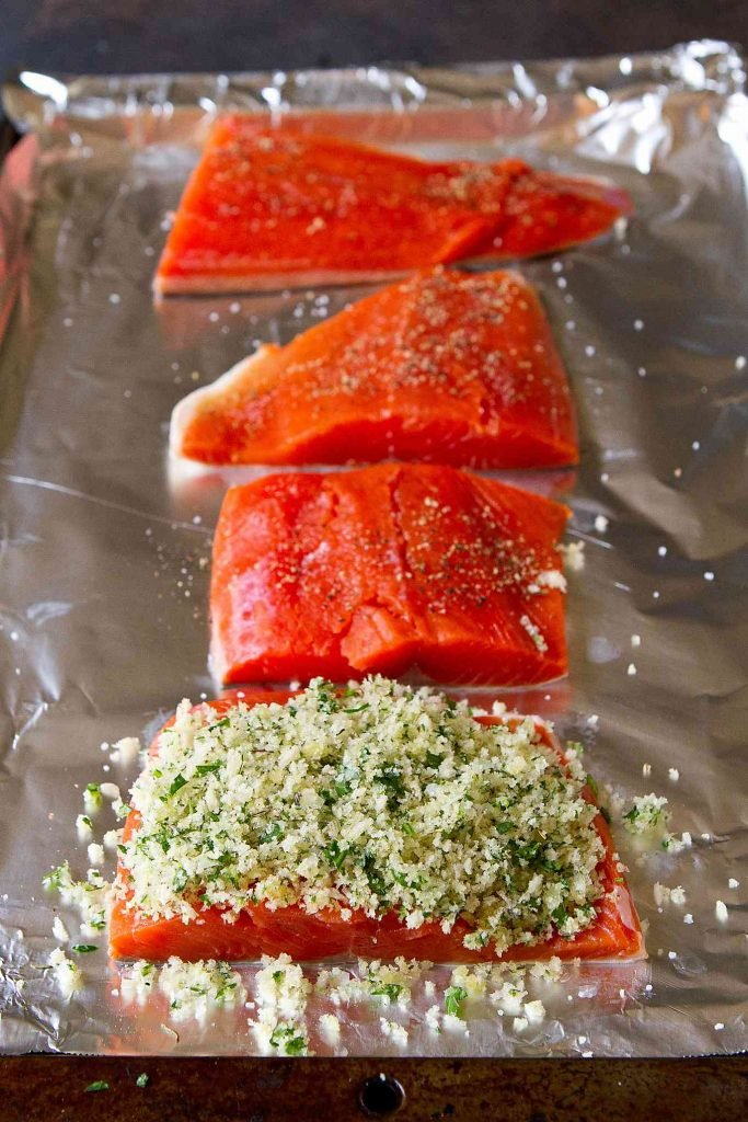 Salmon fillets on a baking sheet. Fillet in foreground topped with a breadcrumbs and herb topping.