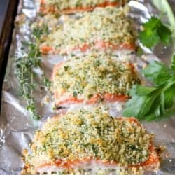 Salmon fillets on a foil-lined baking sheet, each topped with herb Parmesan crust