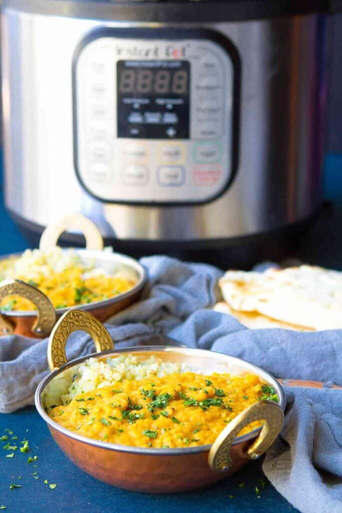 Red lentil dal in a brass bowl, with an Instant Pot in the background.