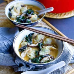 Wonton soup with mushrooms and chard in bowls. Spoons and chopsticks on the side.