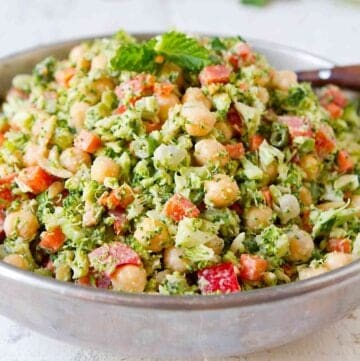 Chopped broccoli salad with chickpeas and other vegetables in a silver bowl.
