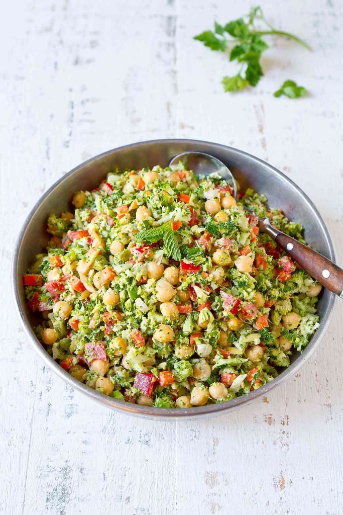 Chopped broccoli salad with red pepper, chickpeas and carrot in a silver bowl.