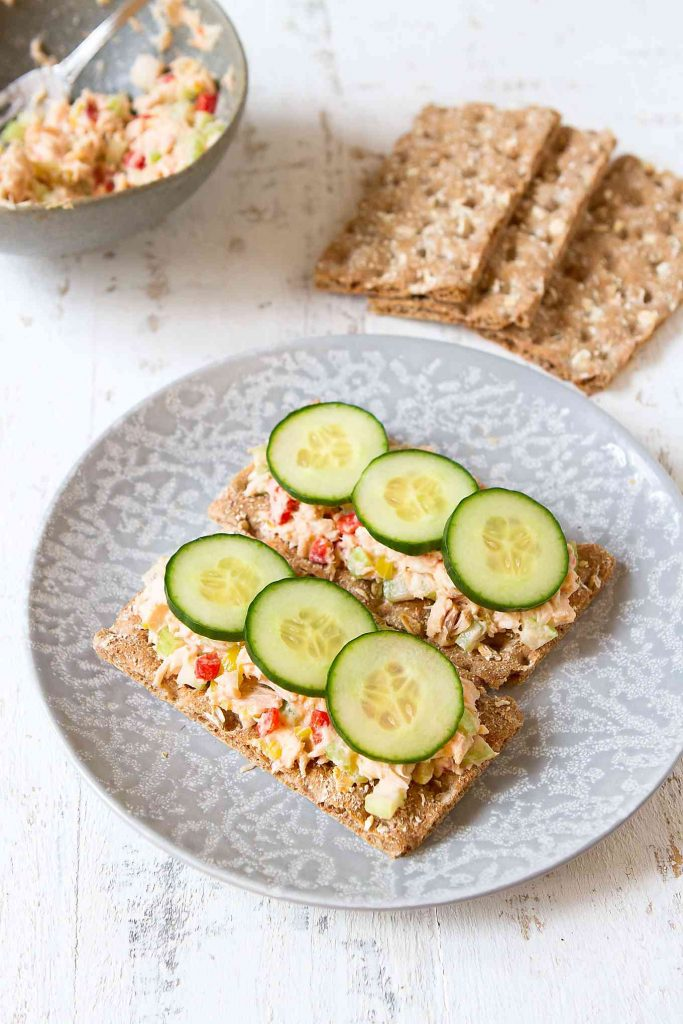 Tuna salad on crackers with cucumber on a gray plate