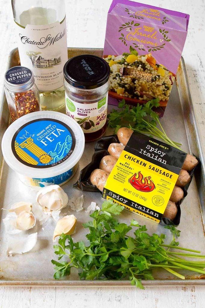 Box of pearl couscous, sausage, feta, wine, garlic, feta and parsley on a baking sheet.